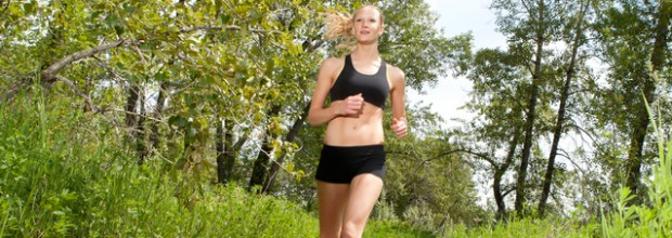 Young woman jogging outdoors in summer on trail